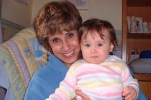 A grandma holding her toddler granddaughter.