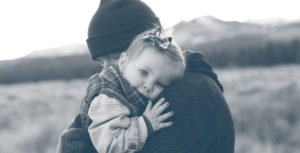 A dad hugs his toddler daughter.