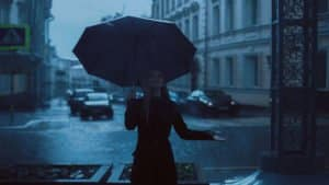 A woman stands under and umbrella looking up at the pouring rain.