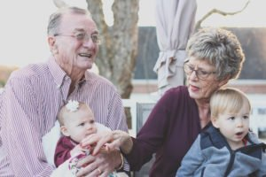 Grandparents holding their grand children.