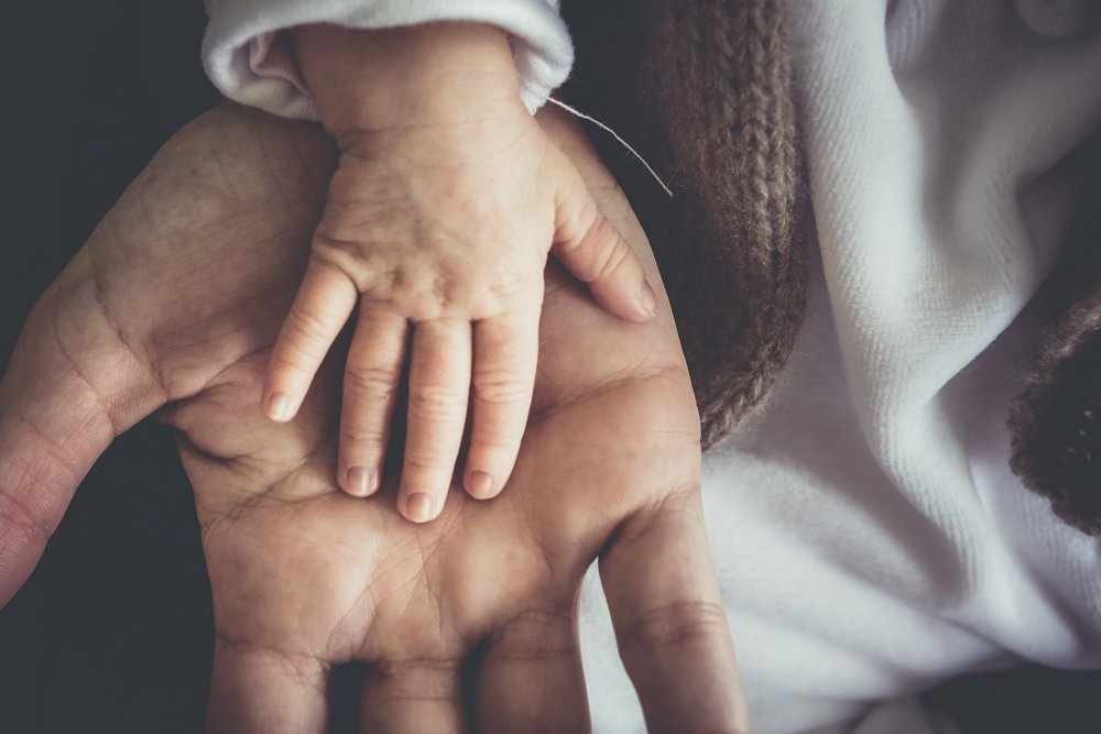 A small child's hand in the palm of a man's hand.