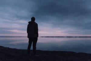A man stands at the edge of the lake at sundown.