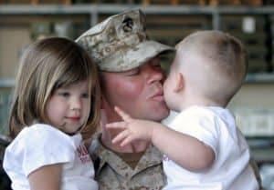 A soldier kisses his children.