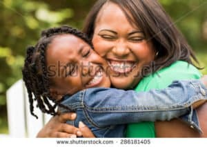 An African-American mother hugging her daughter.