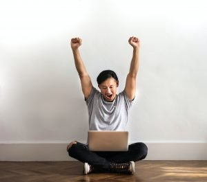 A man raises his arms in excitement looking at his laptop.