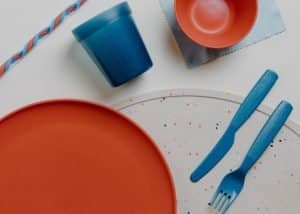 A child's plate, cup, straw, knife and fork.