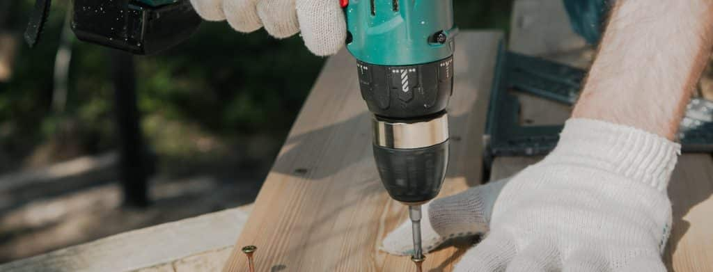 A man drills a screw into a piece of lumber.